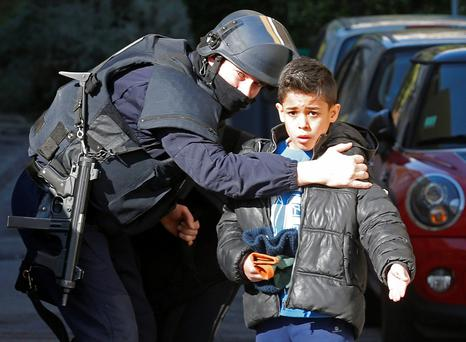 A French police officer speaks to a frightened boy outside a school in the Castellane housing area in Marseille yesterday after hooded men fired on police