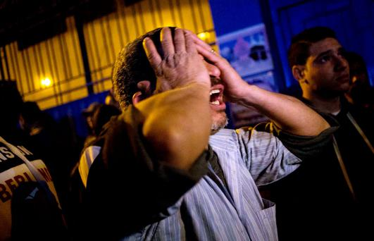 A bereaved father grieves for his dead sons at the Zynhom morgue in Cairo