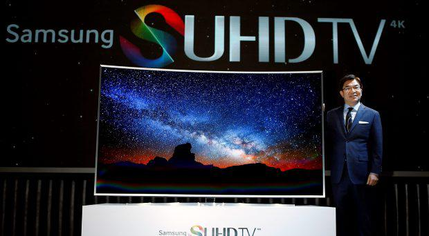 Kim Hyun-seok, head of Samsung Electronics' television division, poses for photographs with a Samsung Electronics S'UHD smart TV during its launch event