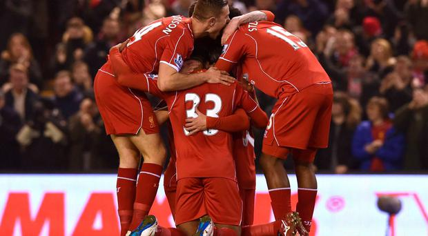 Jordon Ibe, Jordan Henderson and striker Daniel Sturridge crowd around Liverpool's Serbian midfielder Lazar Markovic (obscured) after he scored the opening goal against Tottenham Hotspur at Anfield