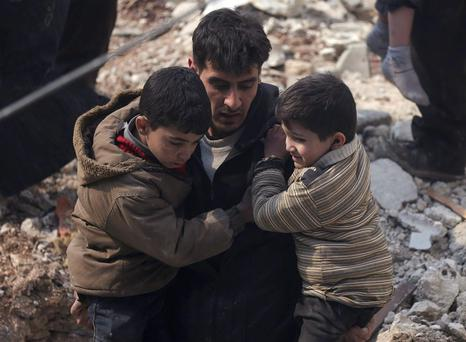 A man carries children rescued from an area which activists said were hit by airstrikes from forces loyal to Syria's President Bashar al-Assad in the Douma neighborhood of Damascus