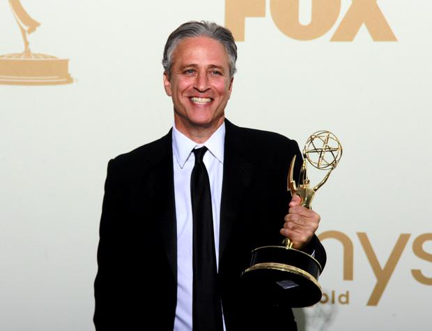 Television host Jon Stewart holds the Emmy award for the