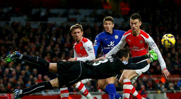 Arsenal's Arsenal's David Ospina makes a save as team mates Laurent Koscielny (R) Per Mertesacker (L) and Leicester City's Andrej Kramaric watch during their English Premier League soccer match at the Emirates Stadium