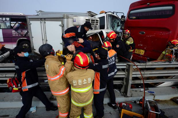 Firefighters rescue an injured man from a damaged vehicle on Yeongjong Bridge in Incheon February 11, 2015. A traffic pileup involving more than 100 vehicles on the bridge on Wednesday killed at least two people and injured more than 30 people, according to local news reports. REUTERS/Park Jung-ho/News1