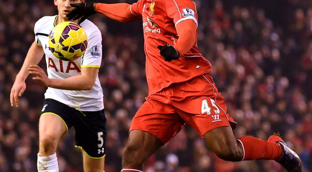 Liverpool's Italian striker Mario Balotelli clears the ball during the English Premier League football match between Liverpool and Tottenham Hotspur at the Anfield stadium in Liverpool