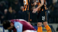 Hull City's Michael Dawson (right) and Paul McShane celebrate as Aston Villa's Joe Cole acts dejected after the Barclays Premier League match at the KC Stadium last night