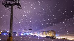 Night on ski and snowboard resort Pas de la casa, Andorra with ski lift, snowfall and illuminated village.