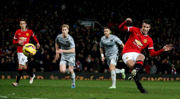 Manchester United's Robin van Persie scores his team's third goal from a penalty against Burnley at Old Trafford.