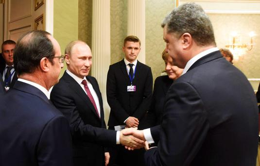 Russia's President Vladimir Putin (2nd L) shakes hands with his Ukrainian counterpart Petro Poroshenko, with France's President Francois Hollande (L) and Germany's Chancellor Angela Merkel standing nearby, as they take part in peace talks on resolving the Ukrainian crisis in Minsk