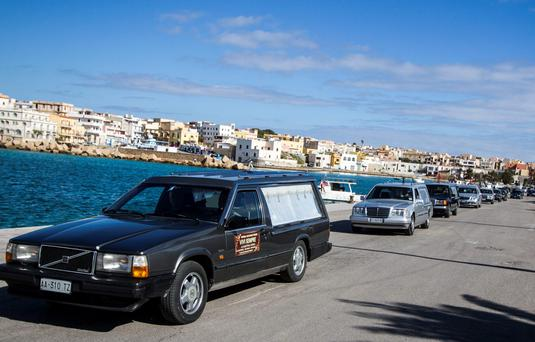A long line of hearses carrying the coffins of 29 migrants who died from hypothermia during a voyage from Libya is pictured in Lampedusa, Italy. Some 300 migrants who tried to cross the frigid Mediterranean in open, rubber boats, were reported missing by survivors