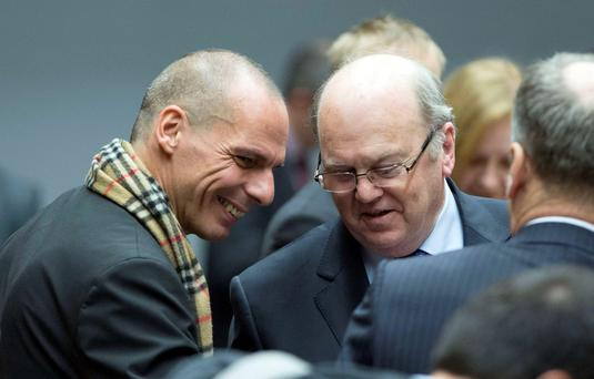 Irish Finance Minister Michael Noonan (L) talks with his Greek counterpart Yanis Varoufakis during an extraordinary Euro zone Finance Ministers meeting to discuss Athens' plans to reverse austerity measures agreed as part of its bailout, in Brussels