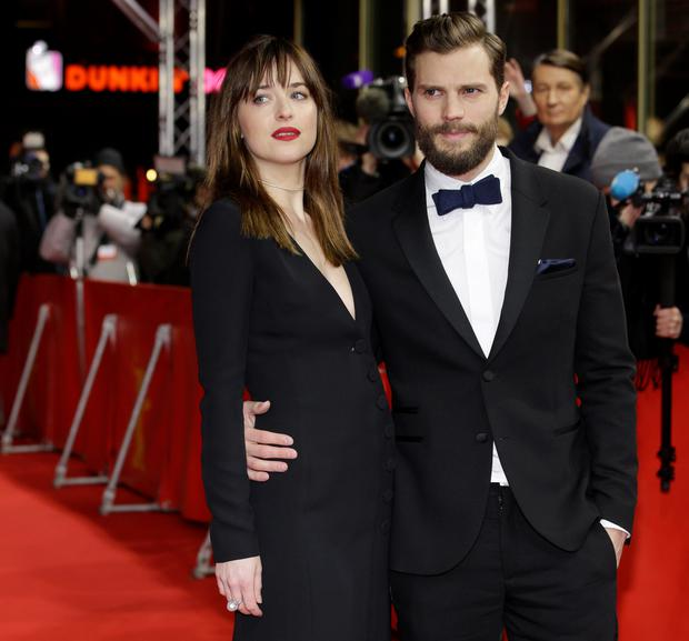 Actress Dakota Johnson, left, and actor Jamie Dornan pose for photographers on the red carpet for the world premiere of Fifty Shades of Grey at the 2015 Berlinale Film Festival in Berlin, Wednesday, Feb. 11, 2015. (AP Photo/Michael Sohn)