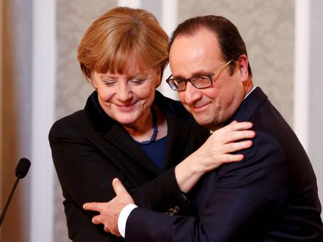 Germany's Chancellor Angela Merkel (L) embraces France's President Francois Hollande during a meeting with the media after peace talks on resolving the Ukrainian crisis in Minsk. Reuters