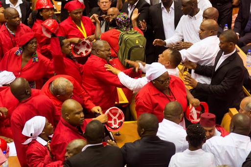 Members of the Economic Freedom Fighters, wearing red uniforms, clash with security forces during South African President's State of the Nation address in Cape Town. Photo: AFP