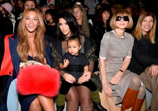 North West does NOT do cutesy dresses on mommy's lap during Fashion Week - she does bulletproof vests and pouts.