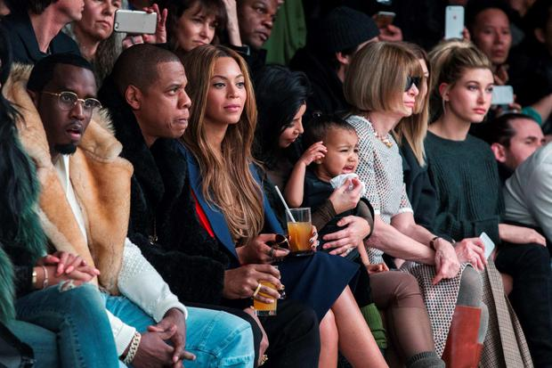 Kim Kardashian attempts to calm her daughter, North, while sitting next to Sean Combs, Jay-Z, Beyonce and Anna Wintour as they watch a presentation of Kanye West's Fall/Winter 2015 partnership with Adidas at New York Fashion Week February 12, 2015. REUTERS/Lucas Jackson