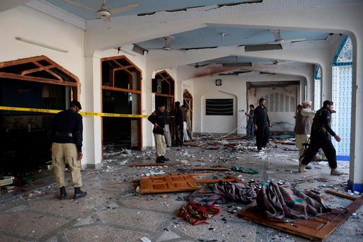 Pakistani security personnel inspect a Shiite Muslim mosque