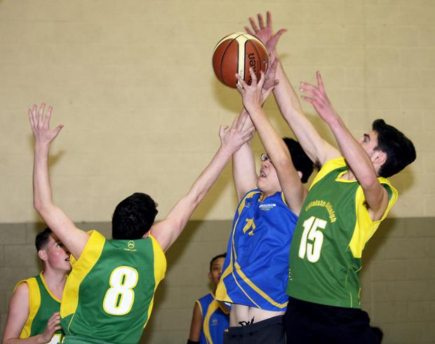 Darren Byrne and Sean Nolan, Colaiste Dhulaigh try to stop Larkin's Kaiwen Yang