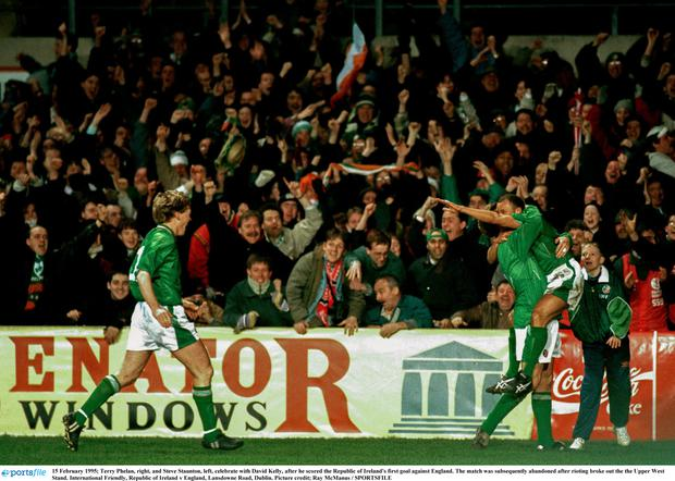 Terry Phelan, right, and Steve Staunton, left, celebrate with David Kelly, after he scored the Republic of Ireland's first goal against England.