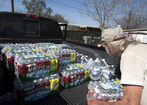 A man carries drinking water as water wells supplying hundreds of residents remain dry in the fourth year of worsening drought in East Porterville, California.