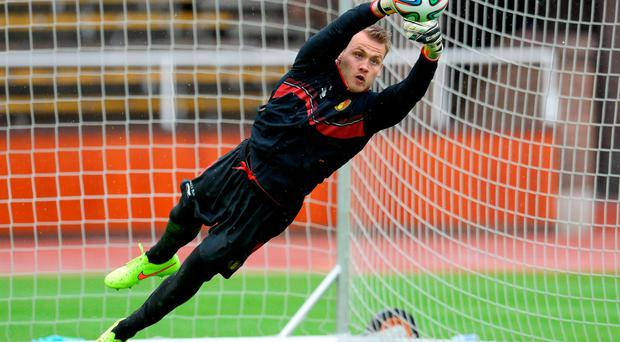 Simon Mignolet holds the ball during a training session