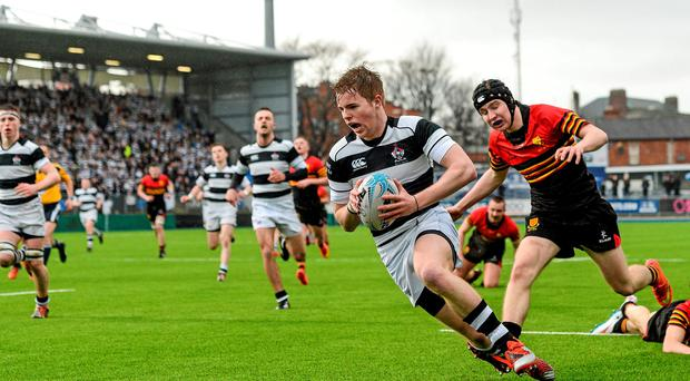Conor Jennings, Belvedere College, goes past the tackle of Shane Sweeney, CBC Monkstown, on his way to scoring his side's first try.
