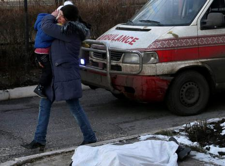 A woman carrying a child walks past the body of a child covered with a cloth after shelling between Russian-backed separatists and Ukrainian government forces in a residential area of the town of Artemivsk, Ukraine