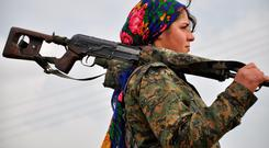 A Kurdish female fighter of the People's Protection Units (YPG) looks on at a training camp in al-Qahtaniyah. Syrian Kurdish forces have recaptured more than a third of the villages around Kobane from the Islamic State group