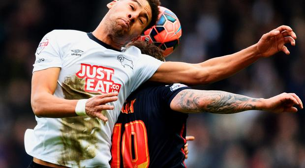 Derby County's Ryan Shotton jumps with Simon Cox of Reading during their FA Cup fifth round match at the iPro Stadium