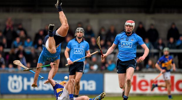 Dublin's Conal Keaney, with team mate Colin Cronin, right, tumbles over Shane McGrath, Tipperary