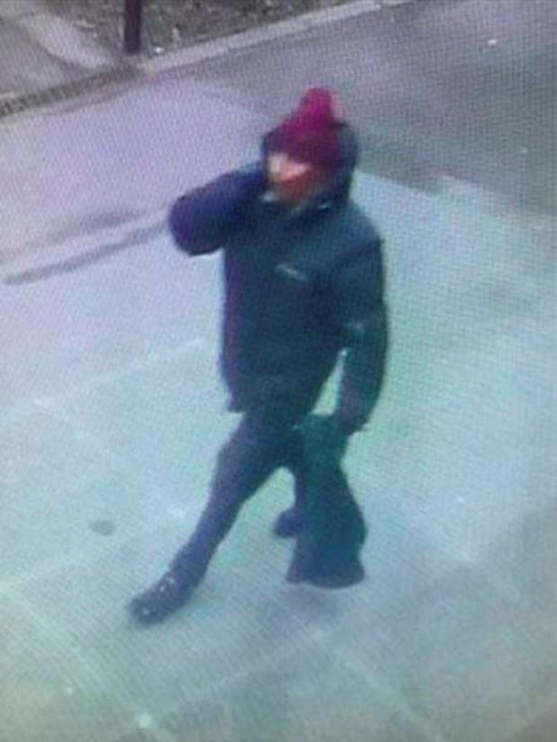 Police-issued image of the suspect gunman, wearing dark clothes and a scarf over his face