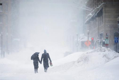 A couple stroll down a deserted street during a winter blizzard in Boston. Photo: REUTERS/Brian Snyder