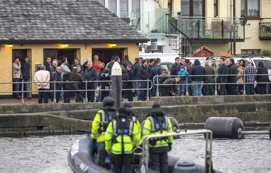 Members of the Garda water unit on the River Shannon in Athlone observe the removal of Barney McGinley, who was shot outside a wedding in Fermanagh. Photo:Mark Condren.