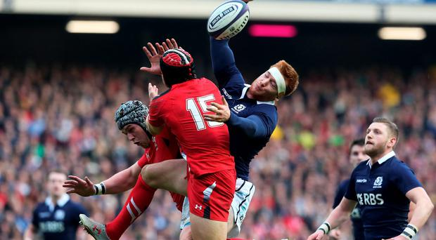 Rob Harley of Scotland competes for a high ball with Dan Lydiate and Leigh Halfpenny