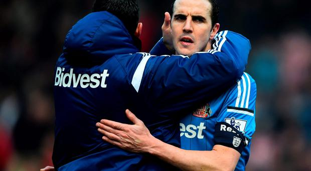 John O'Shea is consoled by Gus Poyet after defeat in the FA Cup Fifth Round