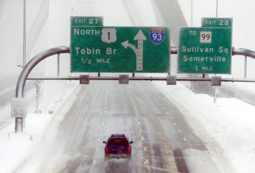 A lone car drives over the Zakim Bridge in Boston after a storm brought a new round of wind-whipped snow as people contended with a fourth winter onslaught in less than a month. Photo: AP Photo/Michael Dwyer