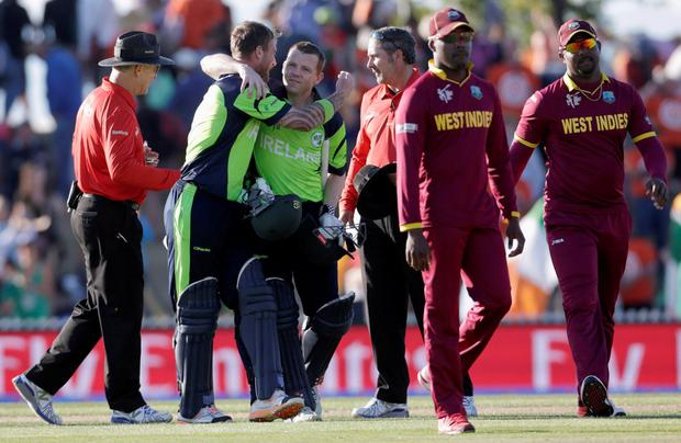 Ireland's John Mooney (2nd L) hugs teammate Niall O'Brien (3rd L) after beating the West Indies for the first time in their Cricket World Cup match in Nelson, February 16, 2015. REUTERS/Anthony Phelps