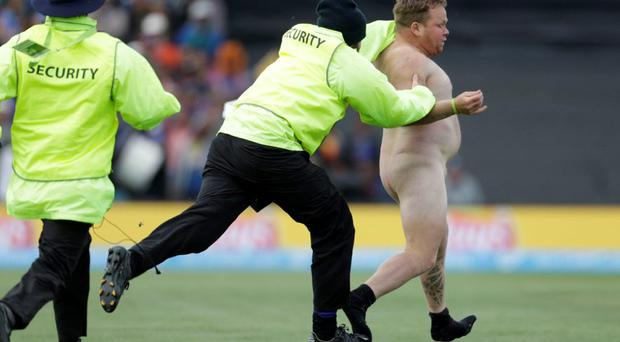 Security personnel chase a streaker who invaded the pitch during the Cricket World Cup match between New Zealand and Sri Lanka in Christchurch, February 14, 2015. REUTERS/Anthony Phelps (NEW ZEALAND - Tags: SPORT CRICKET) TEMPLATE OUT