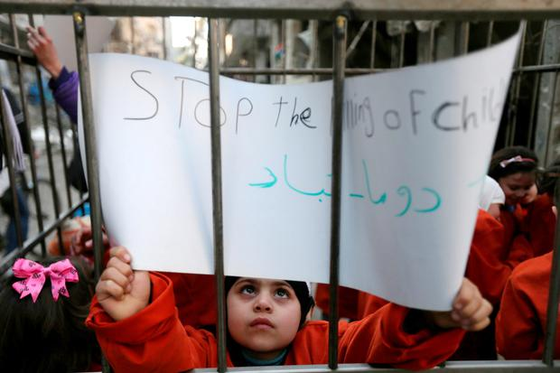 Children carry signs inside a cage during a protest against forces loyal to Syria's President Bashar al-Assad, in Douma Eastern Al-Ghouta, near Damascus, February 15, 2015. REUTERS/Bassam Khabieh