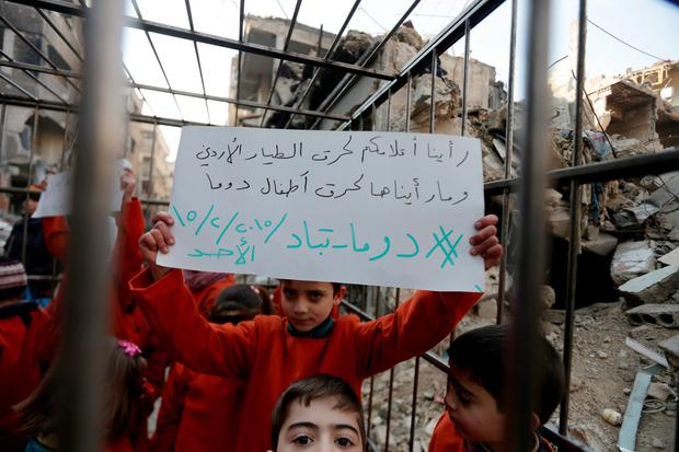 Children carry banners inside a cage during a protest, against forces loyal to Syria's President Bashar al-Assad, in Douma Eastern Al-Ghouta, near Damascus, February 15, 2015. REUTERS/ Bassam Khabieh