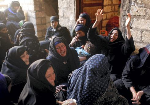 Relatives of Egyptian Coptic men killed in Libya mourn at their house in El-Our village, in Minya governorate, south of Cairo