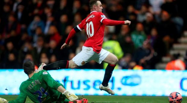Preston's Thorsten Stuckmann (L) concedes a penalty against Manchester United's Wayne Rooney