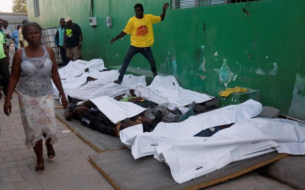 A woman walks away from bodies after failing to find a missing family member among them outside the morgue at the General Hospital in Port-au-Prince, Haiti, Tuesday, Feb. 17, 2015. (AP Photo/Dieu Nalio Chery)