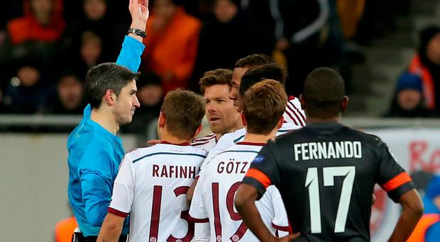 Xabi Alonso is shown a red card by referee Alberto Undiano Mallenco during Bayern Munich's Champions League round-of-16 encounter with Shakhtar Donetsk at the Donbass Arena. Photo: Alexander Hassenstein/Bongarts/Getty Images