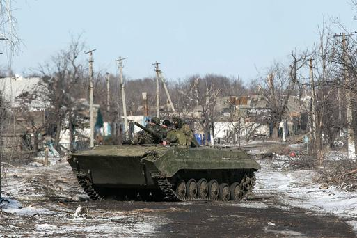 Fighters with the separatist self-proclaimed Donetsk People's Republic army sit on top of an armoured personnel carrier as they head back to the frontline from the village of Nikishine, south east of Debaltseve, Ukraine (REUTERS/Baz Ratner)