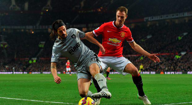 George Boyd of Burnley is closed down by Jonny Evans of Manchester United during the Barclays Premier League match between Manchester United and Burnley at Old Trafford
