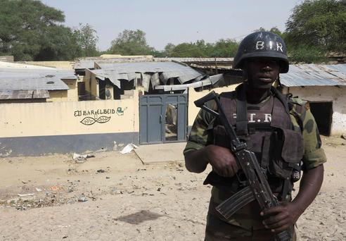 A soldier in the Cameroon stands guard after a Boko Haram attack.