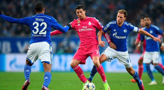 Real Madrid goalscorer Cristiano Ronaldo is challenged by Schalke 04 pair Joel Matip and Benedikt Hoewedes during their Champions League round-of-16 match clash at the Veltins-Arena. Photo: Lars Baron/Bongarts/Getty Images