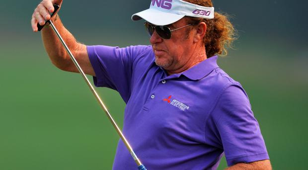 Miguel Angel Jimenez of Spain celebrates a putt by pushing his putter as though he was replacing a sword in it holder during the first round of the Hero India Open Golf at Delhi Golf Club