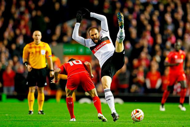 Liverpool's Philippe Coutinho and Veli Kavlak of Besiktas collide during the UEFA Europa League Round of 32 match at Anfield.